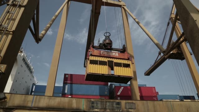 a port worker guides a shipping container as it is lowered by a crane to the dockside at thessaloniki port operated by thessaloniki port authority sa... - straddle carrier stock videos & royalty-free footage