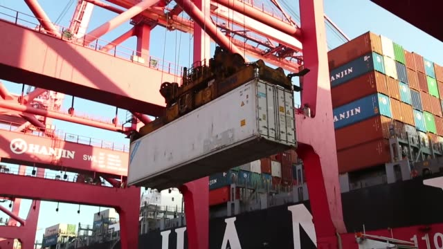 A port worker looks at a notepad as he inspects a container shipment at the Hanjin Shipping Co Busan New Port terminal in Busan South Korea on...