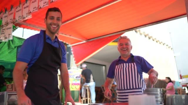 vídeos de stock, filmes e b-roll de portait do pai e do filho que trabalham vendendo o pastel em um mercado de rua - vender