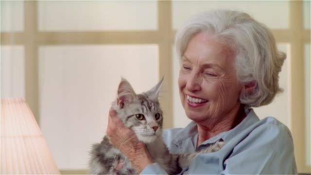 CU ZO portait woman holding Maine Coon cat