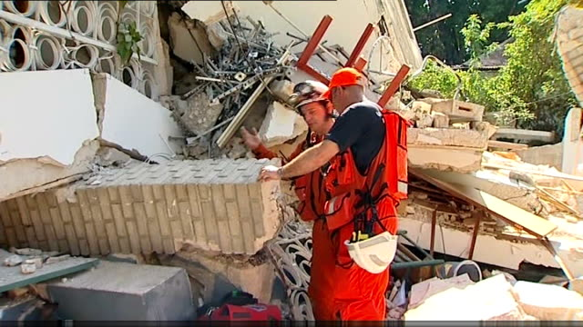 port-au-prince: ext team of british firefighters examining fallen masonry trapping 2-year-old girl mia - rubble stock-videos und b-roll-filmmaterial