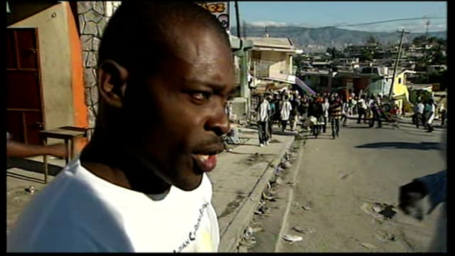 portauprince ext various views of earthquake survivors carrying their belongings and covering their faces to block out the smell of death various... - haiti stock videos & royalty-free footage