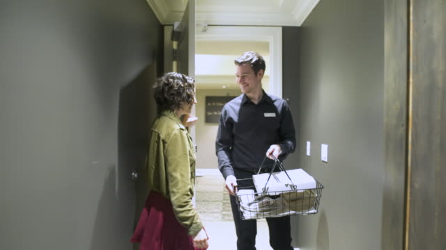 Porter bringing meal to a woman in a hotel
