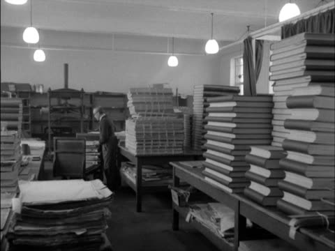 stockvideo's en b-roll-footage met porter pushes a trolley of bound volumes of newspapers at the british museum's newspaper library. - bbc archives