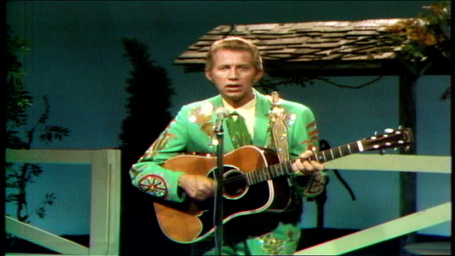 """porter wagoner adjusts the microphone to his height and performs """"the bride's bouquet."""" wagoner sings and plays acoustic guitar. porter wagoner talks... - カウボーイハット点の映像素材/bロール"""