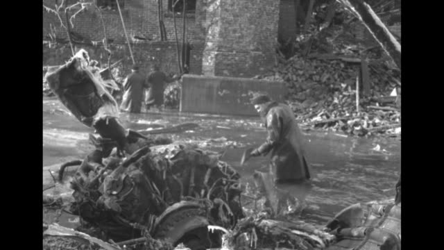 portion of a wing and fuselage with american flag and n1678m in a destroyed structure with three brick chimneys / man in a slicker wades at bank of... - camminare nell'acqua video stock e b–roll