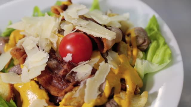 vidéos et rushes de portion de viande salade tournant sur une plaque blanche - salade verte