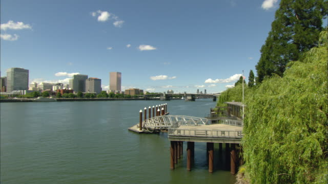 WS Portland cityscape across Willamette River, Morrison Bridge in distance, pier in foreground / Oregon, USA