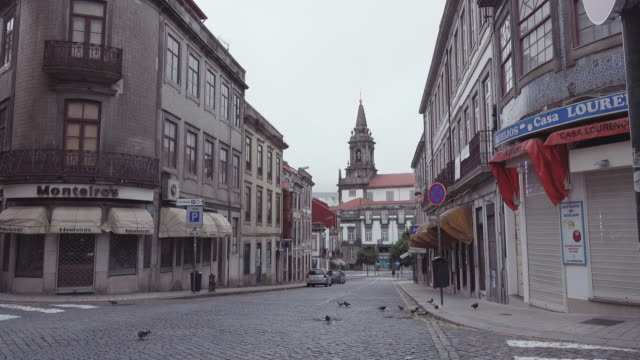 stockvideo's en b-roll-footage met 4k | porto portugal oldtown at early morning. empty streets with the torre dos clerigos tower and church at the end of the slope - kassei