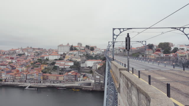 vídeos de stock e filmes b-roll de 4k | porto portugal postcard of the douro river and ponte don luis bridge by eiffel. from vilanova de gaia we can see oporto city. a tram train crosses de shot from left to right amb from right to left at early morning. - parado