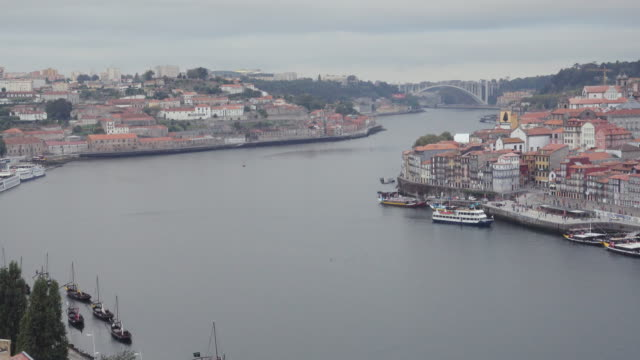 4k | porto portugal postcard of the douro river from ponte don luis bridge build by eiffel. we can see a tourist ship in the middle of the river and the both sides, vila nova de gaia and oporto. - ponte stock-videos und b-roll-filmmaterial