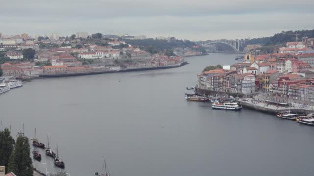vídeos de stock e filmes b-roll de 4k | porto portugal postcard of the douro river from ponte don luis bridge build by eiffel. we can see a tourist ship in the middle of the river and the both sides, vila nova de gaia and oporto. - porto de barcelona