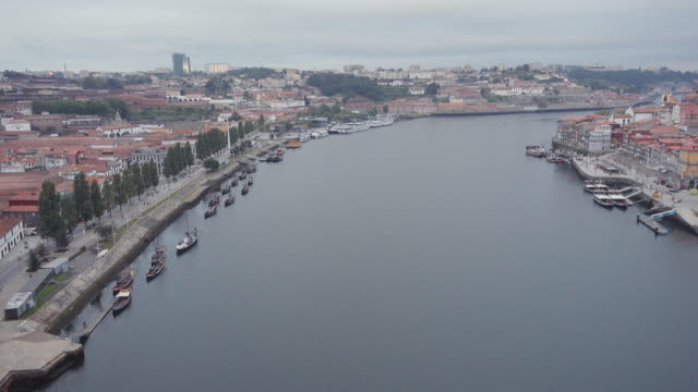 4k | porto portugal postcard of the douro river from ponte don luis bridge build by eiffel. we can see a tourist ship in the middle of the river and the both sides, vila nova de gaia and oporto. - ponte stock videos & royalty-free footage