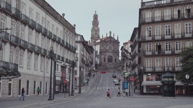 4k | porto portugal postcard of the oldtown at early morning. empty streets with the torre dos clerigos tower and church at the end of the slope - porto district portugal stock videos & royalty-free footage