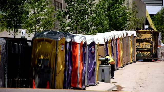 porto potties lined up at construction site for all workers easy access to restroom breaks - urinal stock videos & royalty-free footage