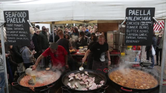 portobello food booth cooks and serves paella a hot seafood dish portobello road market street food on october 01, 2012 in london - portobello mushroom stock videos & royalty-free footage