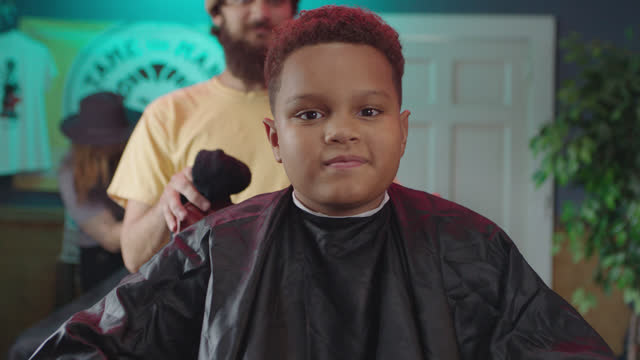 slo mo. portrait. a young boy bobs his head with excitement as he finishes getting his hair cut - hairdresser stock videos & royalty-free footage