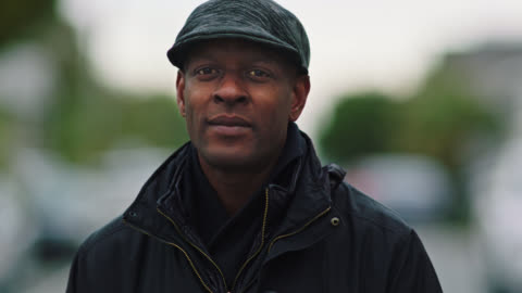 stockvideo's en b-roll-footage met slo mo. portrait. african american man in winter coat and hat softly smiles at camera as he stands in empty neighborhood street on overcast day. - solitair