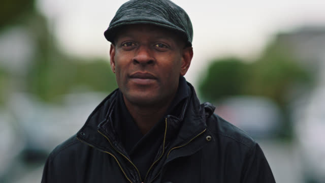 SLO MO. Portrait. African American man in winter coat and hat softly smiles at camera as he stands in empty neighborhood street on overcast day.