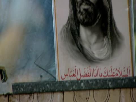 TD Portrait and photo posted in window at produce market / Tehran, Tehran, Iran