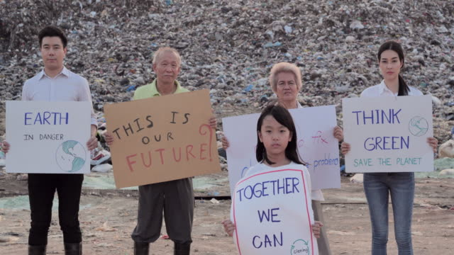 portrait asian family of five volunteers of different age on a huge garbage dump from landfill site in asia and holding posters for environmental movement activists fighting for nature.volunteerism, charity, cleaning,family,ecology concept - holding poster stock videos & royalty-free footage