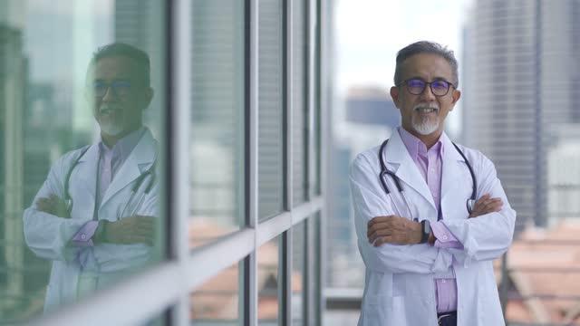 portrait asian senior chinese male doctor outside medical building office - tre fjärdedels längd bildbanksvideor och videomaterial från bakom kulisserna