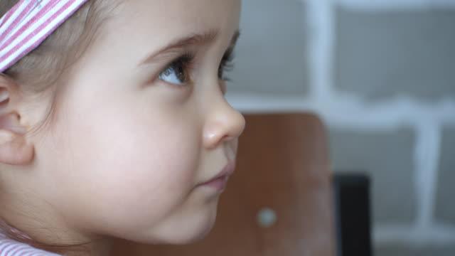 stockvideo's en b-roll-footage met het babymeisje van het portret met bruine ogen die omhoog kijken, close-up - haaraccessoires
