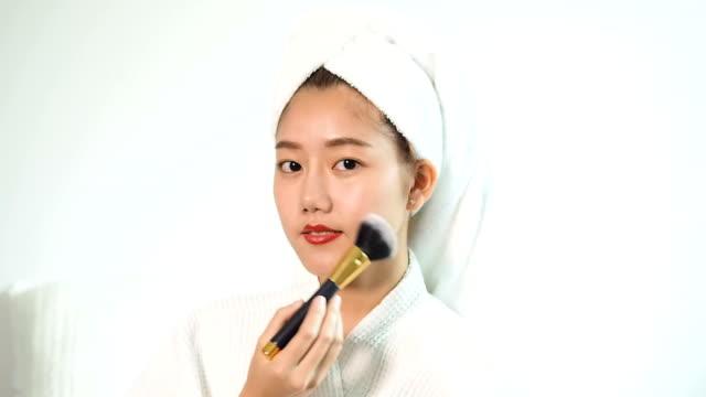 vídeos de stock, filmes e b-roll de retrato a mulher asiática bonita que prende uma escova do blush. mulher nova atrativa que aplica o blush. - blush