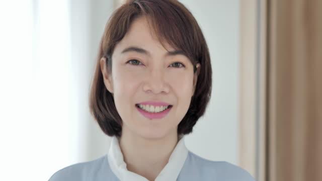 肖像画美しい笑顔自信のあるアジアの若い女性は、成功したライフスタイルを楽しむ幸せな感情で自宅で一人でポーズをとっているカメラを見てかわいい顔。ホームスタジオ - mature adult点の映像素材/bロール