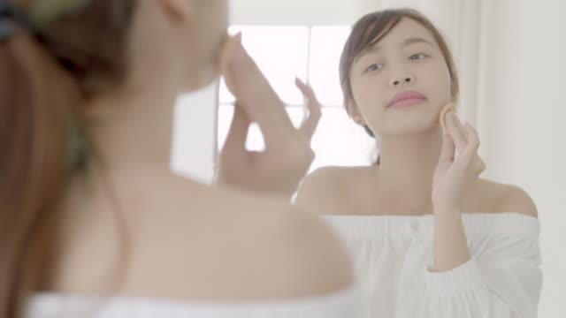 porträtt vacker ung asiatisk kvinna tillämpa pulver puff på kind makeup av kosmetiska söker spegel, livsstil av skönhet flicka med hud ansikte leende i sovrummet, hälsa och wellness koncept. - applicera bildbanksvideor och videomaterial från bakom kulisserna