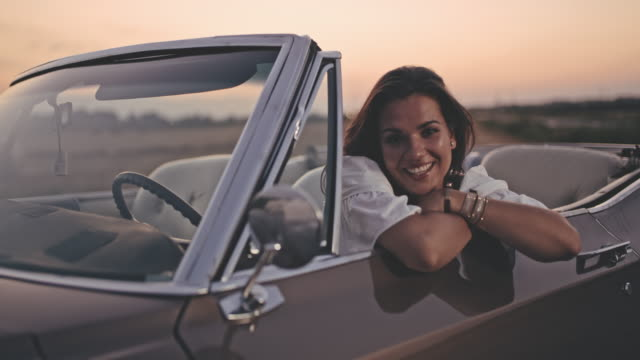 ms portrait beautiful young woman sitting in parked convertible - retro convertible stock videos & royalty-free footage