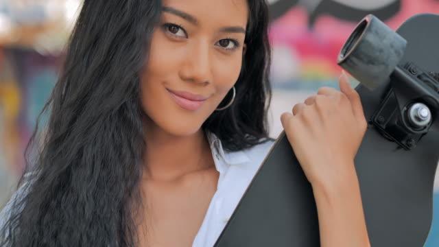 porträt schwarze teenager-mädchen hält ein skateboard blick auf die kamera. lebensstile, extremsport, menschen, führung, portrait, vertrauenskonzept. südostasien und ostasien: junge erwachsene genießen extremsport - east asian ethnicity stock-videos und b-roll-filmmaterial