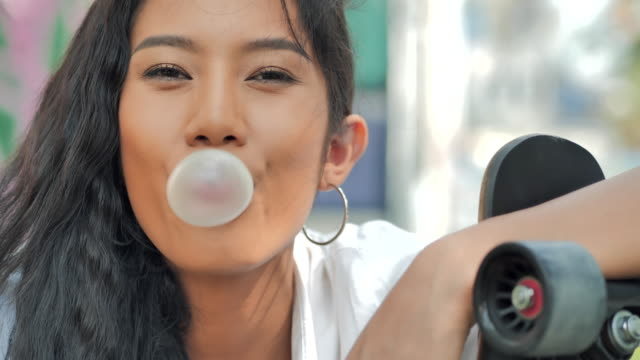 portrait black teenager girl with a skateboard blowing bubblegum candy bubbles and chewing gum.lifestyles, extreme sports, people, leadership, portrait ,confidence concept.south east and east asia: young adults enjoying extreme sports - philippines stock videos & royalty-free footage