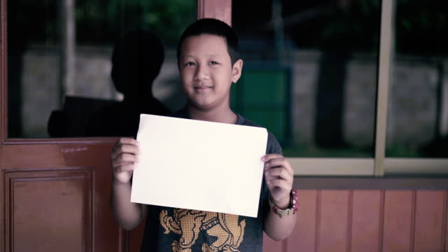 portrait boy holding a white placard - placard stock videos & royalty-free footage