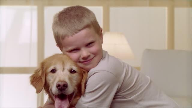 vídeos de stock, filmes e b-roll de ms portrait boy hugging golden retriever - bichos mimados