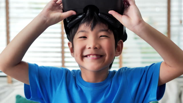 portrait boy wearing virtual reality goggles and smiling.children experiencing virtual reality.surprised little boy looking in vr glasses.education, children, technology, science and people concept - leisure games stock videos & royalty-free footage