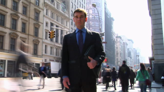 tl ms portrait businessman on street as people pass by/ new york city - stand stock videos & royalty-free footage