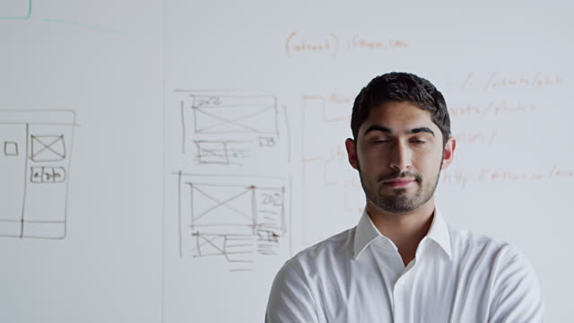 MS R/F portrait businessman standing at workstation in front of white board in  high tech office smiling