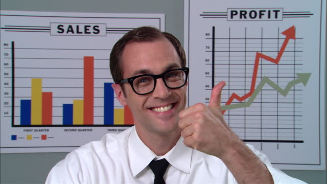 vidéos et rushes de cu portrait businessman with glasses smiling and giving thumbs up in front of graphs/ new york city - tenue d'affaires formelle