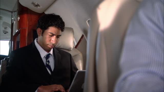 MS Portrait businessman with laptop on corporate jet