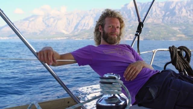 vídeos y material grabado en eventos de stock de 4k retrato despreocupado hombre relajarse, navegar en velero, en tiempo real - velero