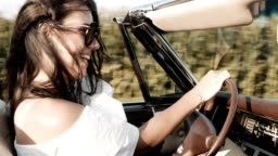 CU Portrait carefree young woman driving convertible along sunny, rural fields