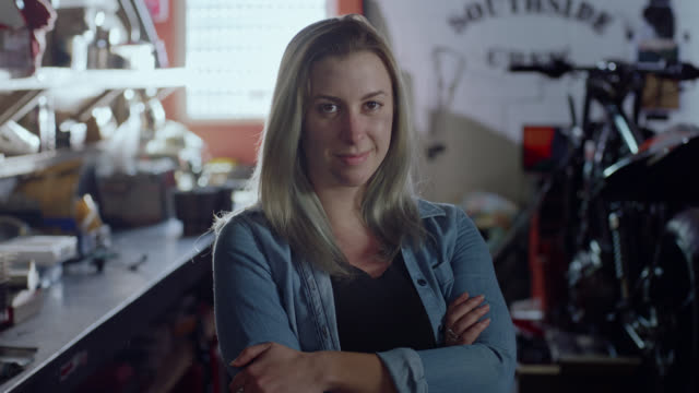 portrait. confident female mechanic in motorcycle shop crosses arms and stares at camera. - stehen stock-videos und b-roll-filmmaterial