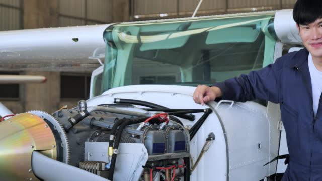 vídeos de stock, filmes e b-roll de retrato, mecânico confiante encara a câmera no hangar do avião. - veículo aéreo