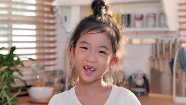 stockvideo's en b-roll-footage met portret dat van aziatisch kindmeisje glimlacht om geen tanden tijdens het bekijken van camera te tonen die alleen thuis met gelukkige emotie stelt die van succesvolle levensstijl geniet. thuisstudio - alleen kinderen