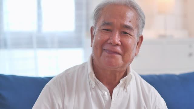 成功したライフスタイルを楽しむ幸せな感情で自宅で一人でポーズをとっているカメラでコミュニケーションしながら微笑むアジアの高齢の祖父の肖像画。ビデオ会議技術に関する社会的な� - 離れた点の映像素材/bロール