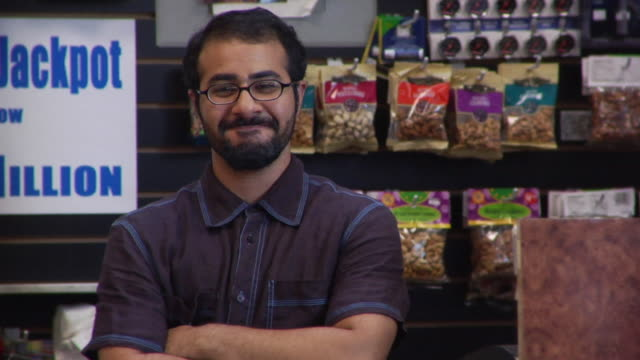 MS portrait convenience store clerk smiling behind counter/ Brooklyn, New York