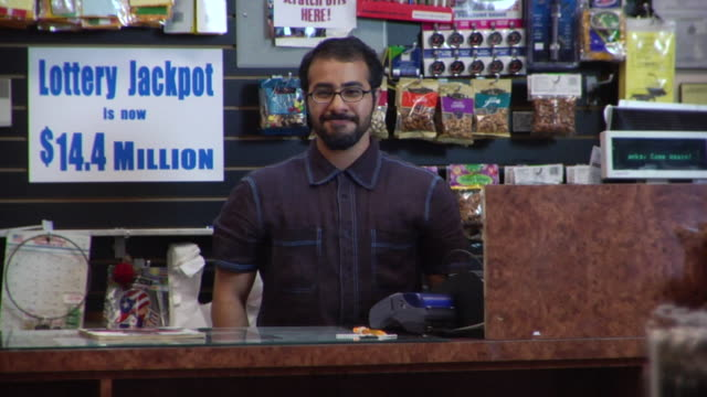 ms portrait convenience store clerk smiling behind counter/ clerk walking off/ brooklyn, new york - shop assistant stock videos & royalty-free footage