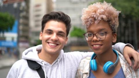 vídeos de stock, filmes e b-roll de casal retrato abraçando na cidade - universidade