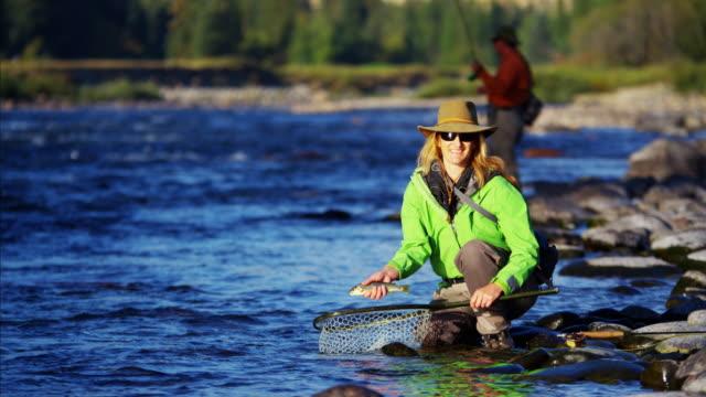 stockvideo's en b-roll-footage met portrait cutthroat trout caught by skilled female canada - hengel uitwerpen